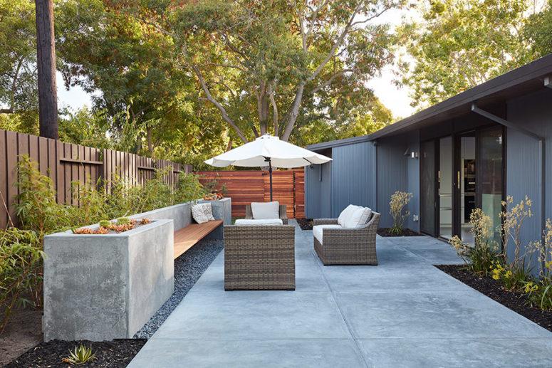 Lo spazio esterno è realizzato con mobili in vimini, un ombrellone e una panchina in cemento con fioriere incorporate