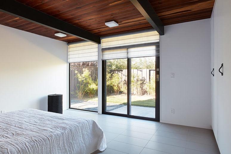Una parete parzialmente vetrata può essere aperta verso l'esterno e coperta con sfumature romane quando i proprietari vogliono un po 'di privacy