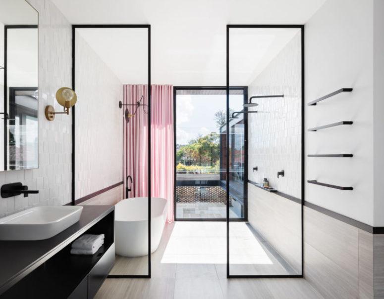 Il bagno è luminoso, arioso e spazioso con tocchi neri e una tenda rosa