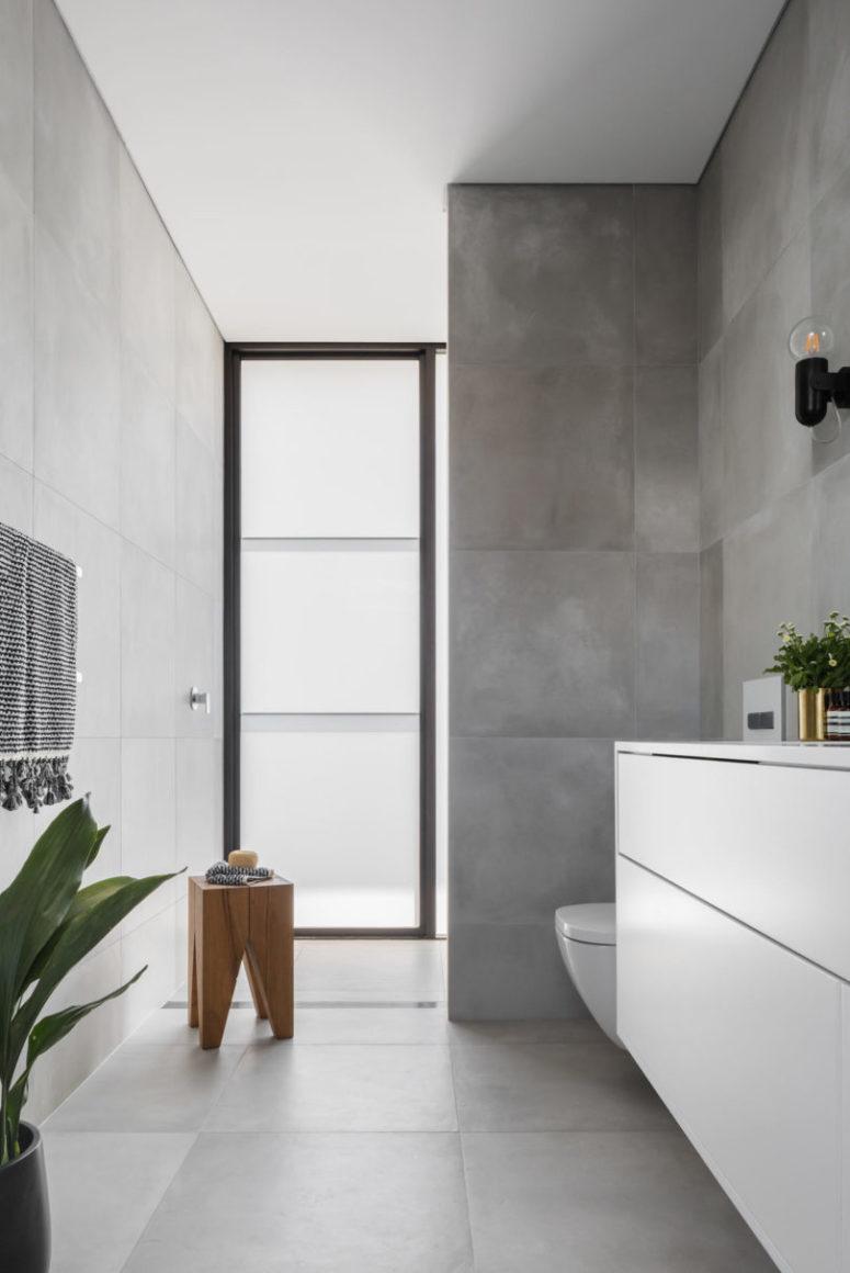 Un altro bagno presenta iles in cemento e una finestra in vetro smerigliato