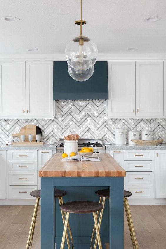 Una cucina bianca con alzatina piastrellata a spina di pesce e cappa blu scuro e isola cucina con piano di lavoro in legno
