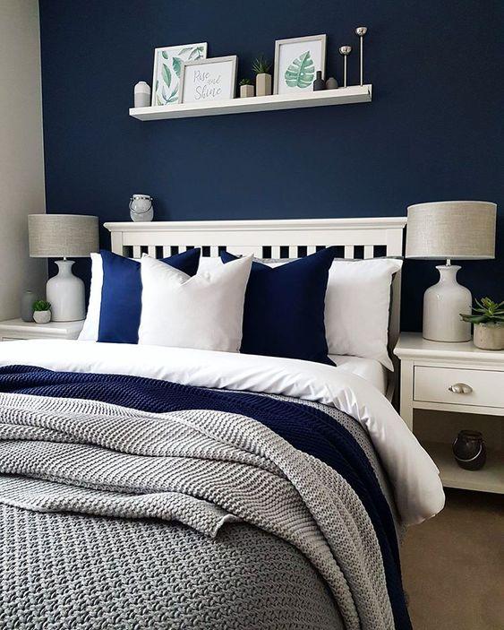 un'accogliente camera da letto in blu scuro, bianco e grigio sembra contrastante, audace ma molto invitante