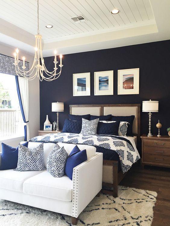 una camera da letto con un muro blu navy, biancheria da letto blu scuro e bianca e un divano cremoso con cuscini blu scuro
