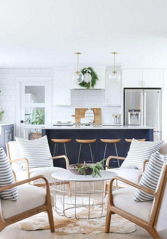Una cucina bianca con un'isola della cucina blu scuro con tocchi in legno e ripiani in pietra per una casa sulla spiaggia