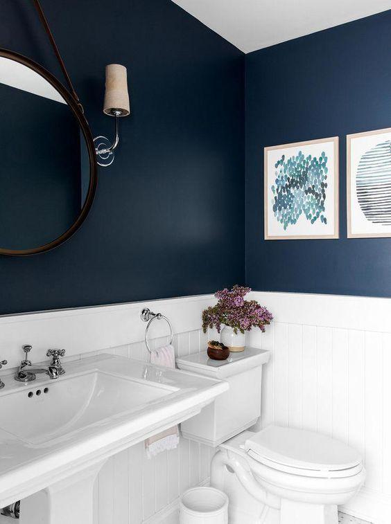 il bagno presenta un aspetto contrastante di pareti blu scuro e elettrodomestici e piastrelle bianche