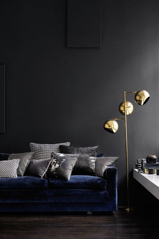 un elegante soggiorno lunatico con pareti grigio grafite, un divano blu scuro e una disposizione di vari cuscini grigi