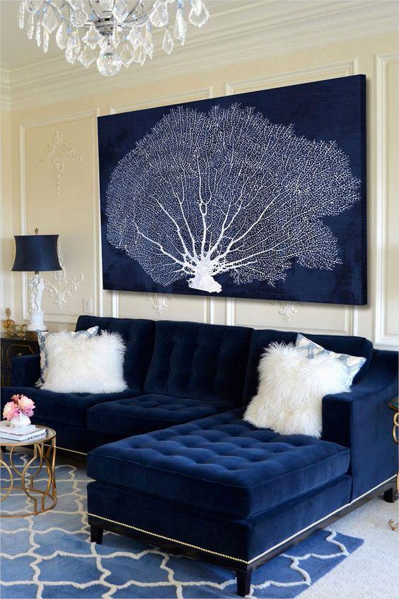 uno spazio nautico con un divano trapuntato blu scuro e una grande opera d'arte in blu navy e bianco che mostra un corallo