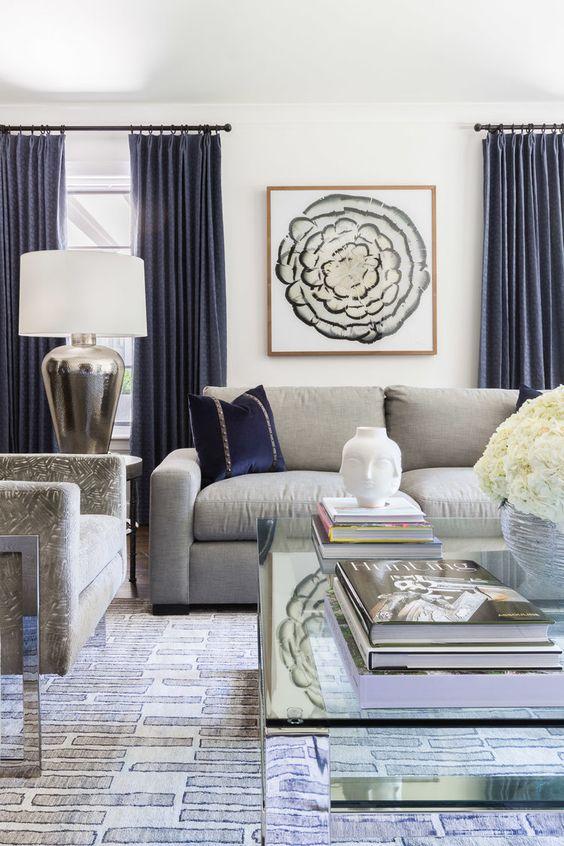 un elegante soggiorno con mobili grigi e cuscini e tende blu scuro creano un aspetto molto chic e raffinato