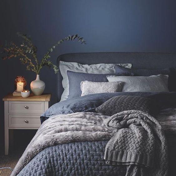 una camera da letto molto accogliente con un muro blu scuro e lenzuola e coperte blu scuro e bianche