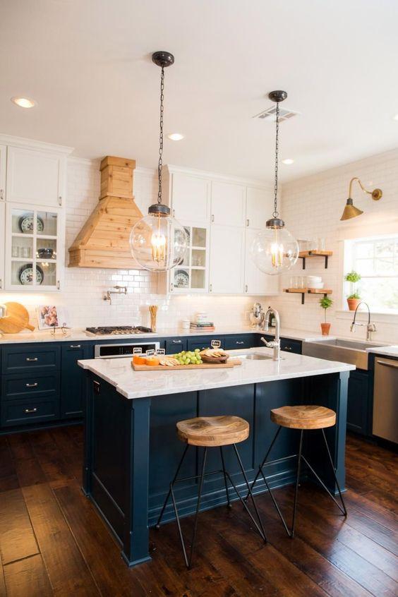 una combinazione di colori chic di blu marino e bianco è ammorbidita e riscaldata con tocchi di legno naturale e lampade a sospensione