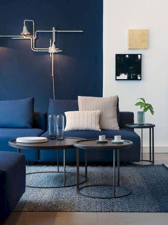 un soggiorno con un muro blu navy, un divano blu scuro e un tappeto grigio più tavolini da caffè