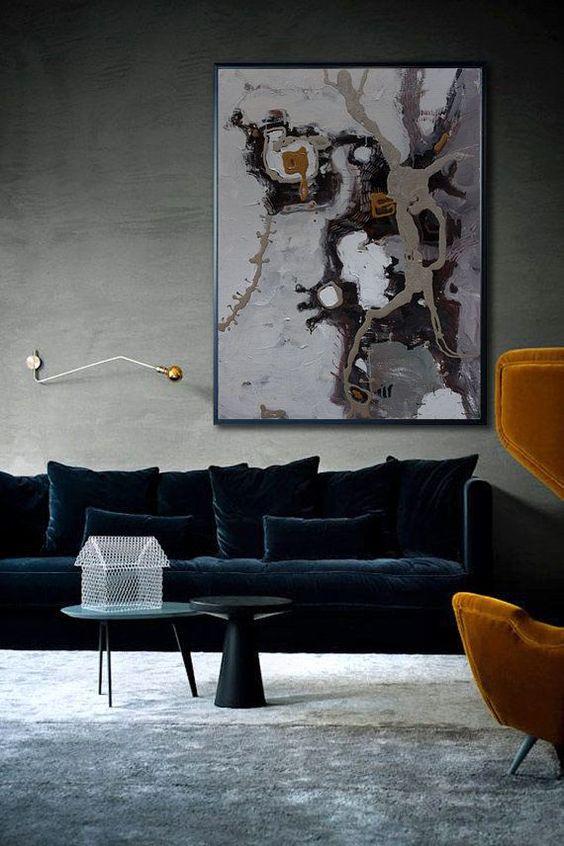 un soggiorno sofisticato con pareti grigie e un pavimento, con un grande divano e cuscini in velluto blu navy refiend