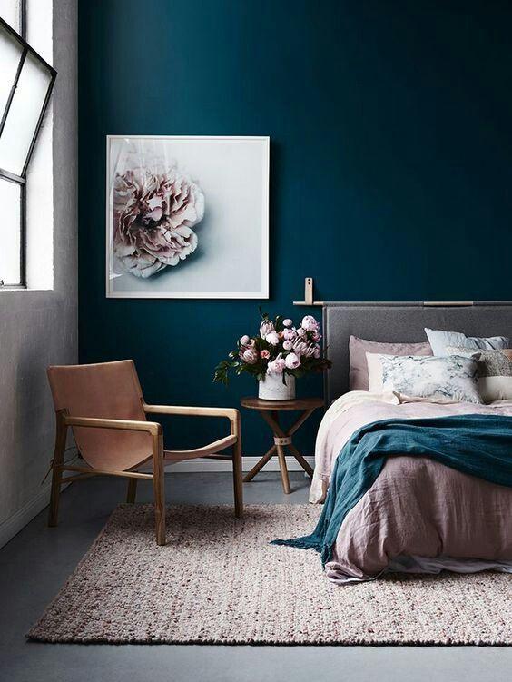 una camera da letto chic con un muro blu scuro, un tappeto arrossato e biancheria da letto sembra molto invitante