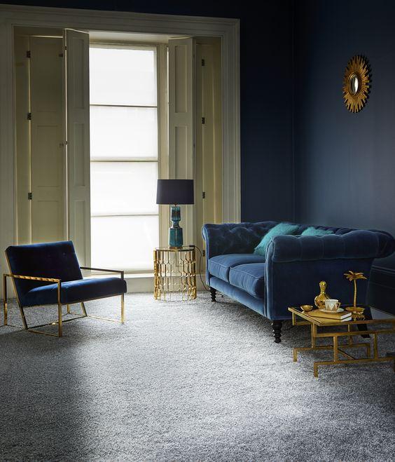 un raffinato soggiorno con un pavimento grigio, una parete blu scuro, un divano e una sedia blu scuro
