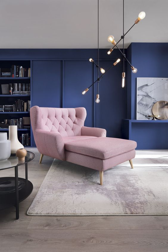 un soggiorno moderno della metà del secolo con pareti blu scuro e un lettino arrossato sembra audace e fresco