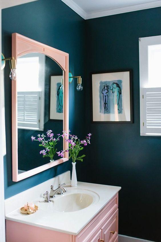 un bagno blu scuro con uno specchio arrossato e una vanità arrossata più tocchi d'ottone qua e là