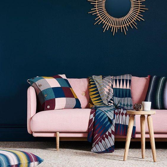 un soggiorno sofisticato con una parete blu navy, un audace divano rosa moderno e accessori colorati