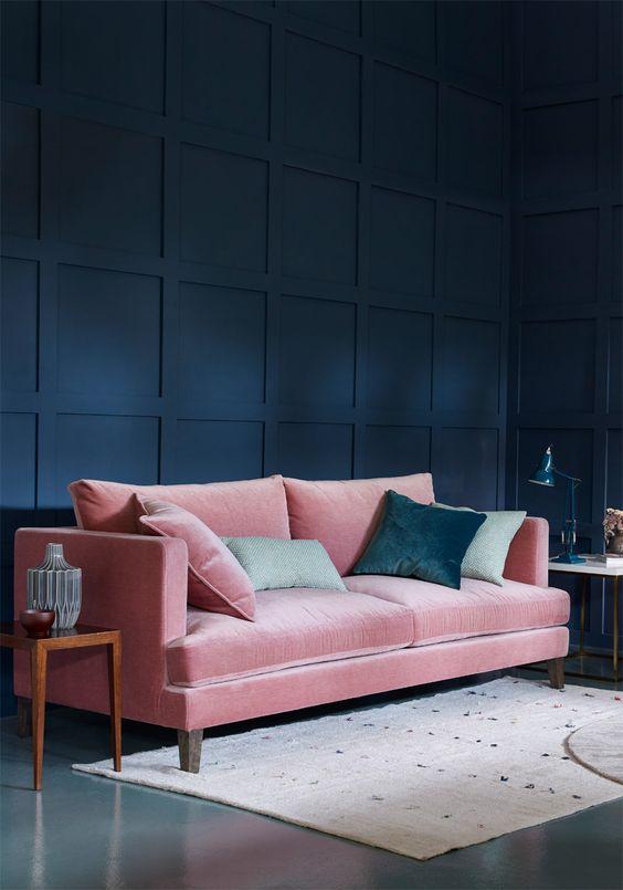 un raffinato soggiorno con una parete blu navy e un divano in velluto rosa più cuscini verdi