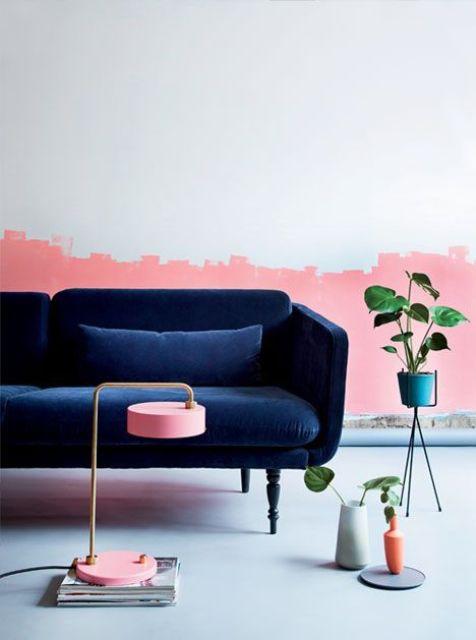 un soggiorno con un'accattivante parete mezza rosa e un raffinato divano in velluto blu scuro