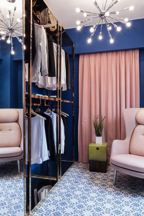 un armadio blu scuro con tende rosa e mobili neutri più tocchi metallici sembra molto glam