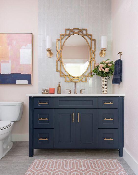 un bagno elegante con una vanità blu scuro, un tappeto stampato arrossato e un'opera d'arte accattivante che li lega entrambi