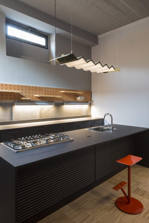 La cucina è realizzata con armadi in metallo nero, un pannello forato con vari ripiani attaccati e una lampada a sospensione