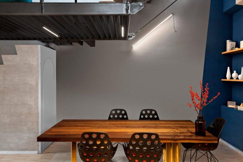 La sala da pranzo presenta decorazioni geometriche, illuminazione industriale, un audace tavolo da pranzo e sedie traforate in metallo