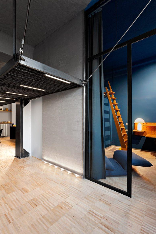 Molta luce, molti dettagli blu e navy, tocchi industriali rendono lo spazio moderno e raffinato