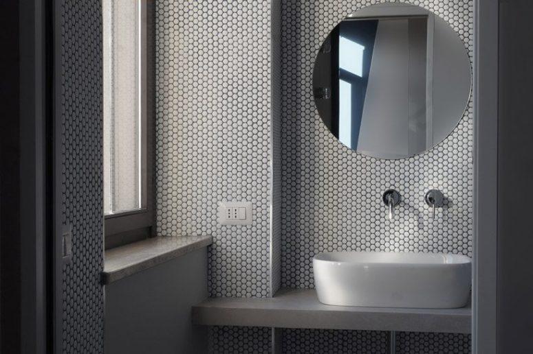 Il bagno è rivestito con piastrelle bianche, c'è un lavandino ovale e uno specchio rotondo