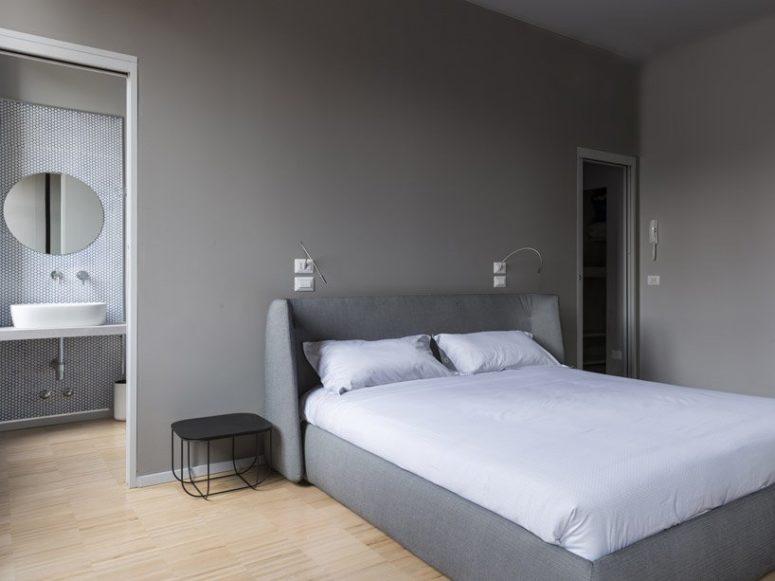 La camera da letto è realizzata nei toni del grigio, con pareti grigie e un letto imbottito grigio e un duo di comodini in metallo