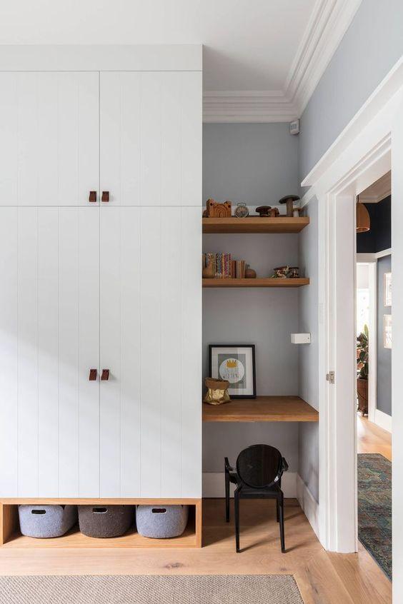 un piccolo angolo dell'ufficio domestico stretto in un angolo, due mensole e una scrivania incorporata