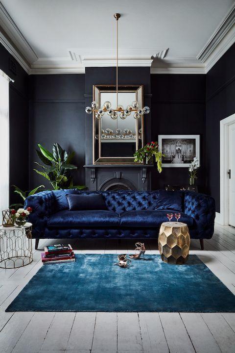 un fantastico e raffinato divano in velluto trapuntato blu scuro aggiunge un tocco e una consistenza lunatici alla stanza