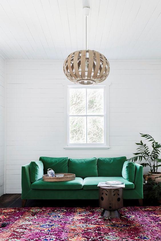 un divano color smeraldo farà sicuramente una dichiarazione audace nel soggiorno e accentuerà molto lo spazio