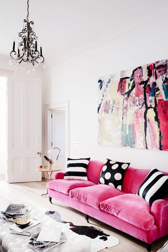 un divano in velluto rosa fa una dichiarazione con la consistenza e con colori vivaci, i cuscini bianchi e neri creano un contrasto