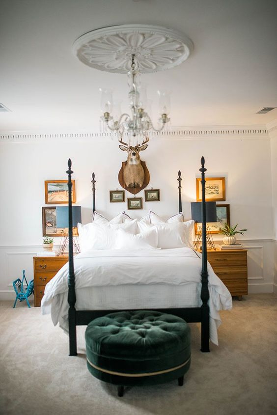 un divano imbottito in velluto verde scuro aggiunge colore e consistenza alla camera da letto neutra