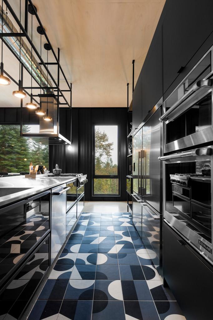 Una cucina lunatica è realizzata con eleganti armadi neri, un pavimento di piastrelle a mosaico in bianco e nero