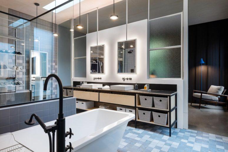 Il bagno è una stanza spaziosa con molta luce, toni di blu e molti specchi