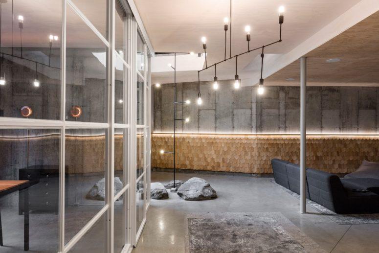 Cemento, singoli in legno, rocce vere e metallo creano un ambiente che è all'aperto e al chiuso