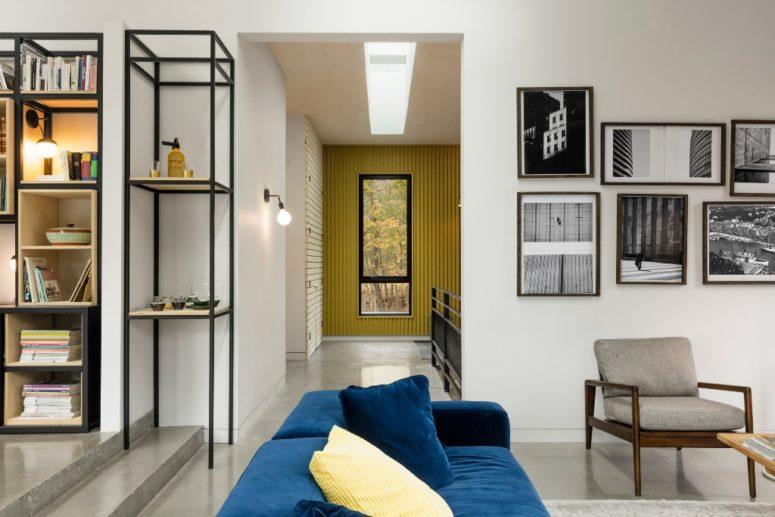 Tocchi audaci come questo divano blu e cuscini gialli aggiungono interesse allo spazio