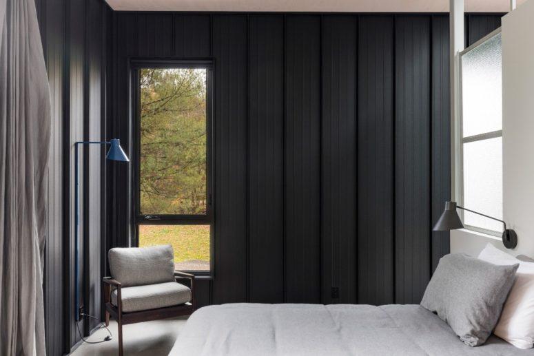La camera da letto presenta anche pareti rivestite in legno nero, le finestre riempiono lo spazio di luce naturale