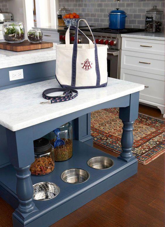 un'isola cucina con un tavolo aggiuntivo e una stazione di alimentazione per cani e un organizzatore di forniture nella sua parte inferiore
