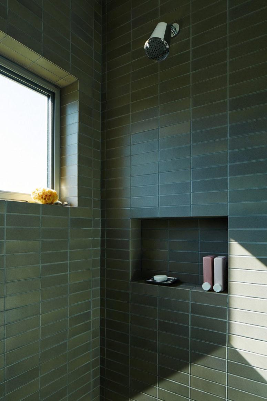 Il bagno è dotato di doccia con piastrelle verde scuro opache lunghe e strette