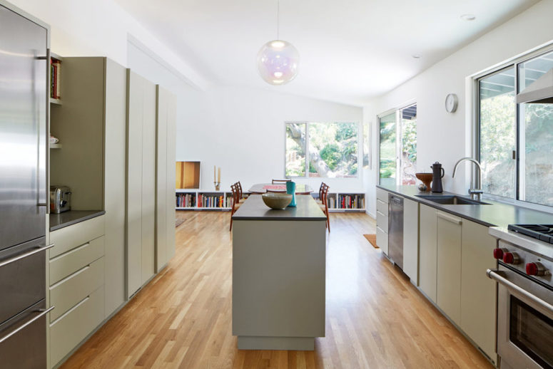 La cucina è realizzata con armadi verde chiaro e ripiani scuri più una grande isola della cucina