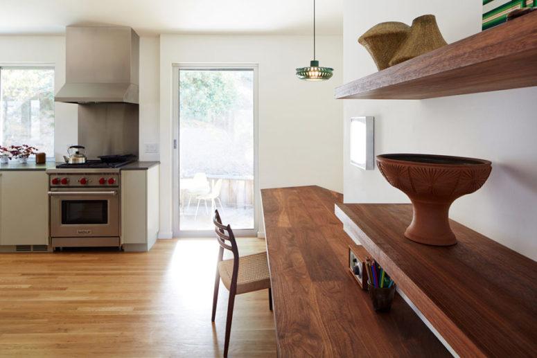 Una parte della cucina è occupata da un comodo ufficio in casa con una scrivania sospesa e scaffali