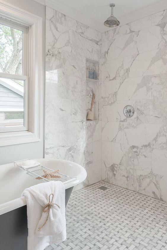 piastrelle di marmo bianco - quelle grafiche sul pavimento e quelle quadrate sulle pareti creano uno spazio armonioso e coeso