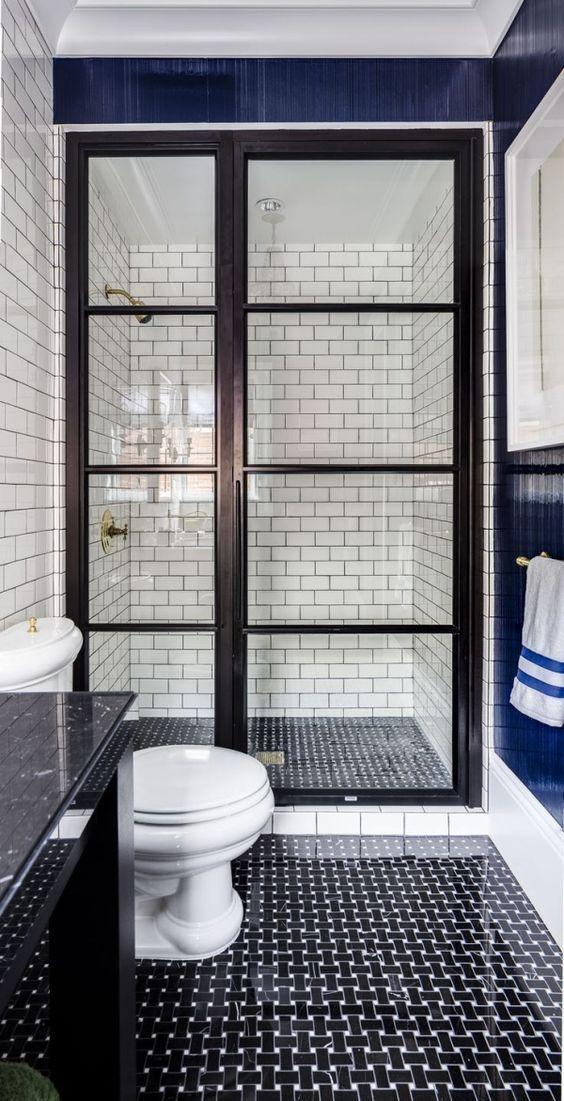 piastrelle grafiche in bianco e nero sul pavimento, piastrelle bianche della metropolitana con stucco nero sulle pareti in una cabina doccia