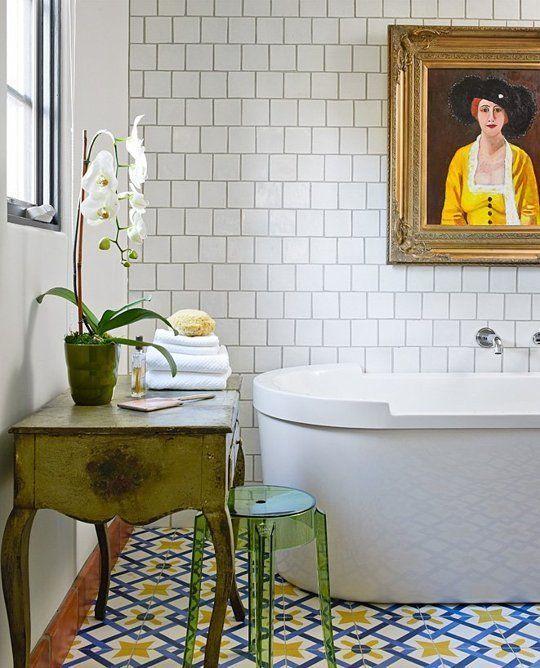 le audaci tessere di mosaico blu e giallo sul pavimento danno il tono al bagno, e le piastrelle bianche sul muro le calmano