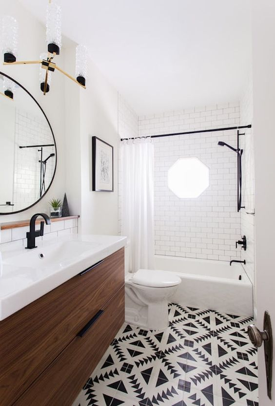 eleganti tessere di mosaico in bianco e nero sul pavimento e piastrelle bianche della metropolitana con stucco nero sulle pareti per un look audace
