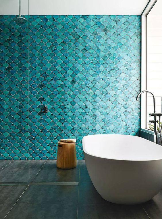 un audace muro di piastrelle in scala di pesce turchese è una dichiarazione in bagno e piastrelle grigie neutre sul pavimento