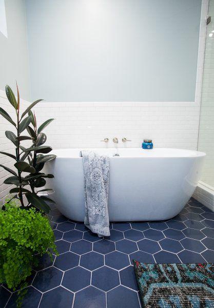 piastrelle esagonali blu scuro sul pavimento e piastrelle bianche sulle pareti creano una combinazione audace e accattivante per un bagno moderno